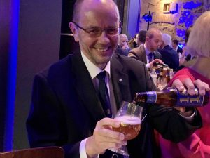Kuvassa mies kaataa olutta lasiin