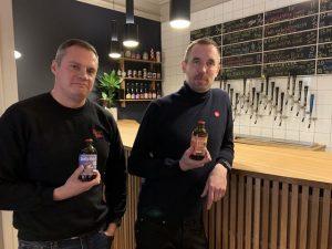 Kaksi miestä pitää Mikkeller olutpulloja