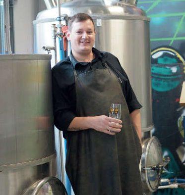 Mies seisoo olutlasi kädessä
