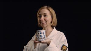 Kuvassa nainen pitää kahvikuppia
