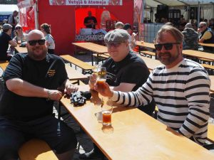 kolme miestä juo olutta