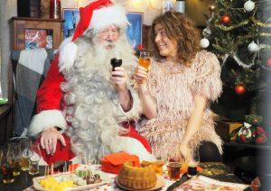 Kuvassa joulupukki ja nainen olutlaseineen