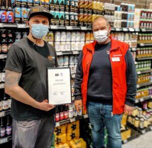 kaksi miestä seisoo olutosastolla