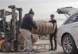 kaksi miestä kantaa viskitynnyriä