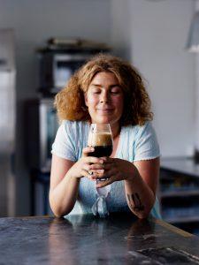 Kuvassa nainen pitelee olutlasia