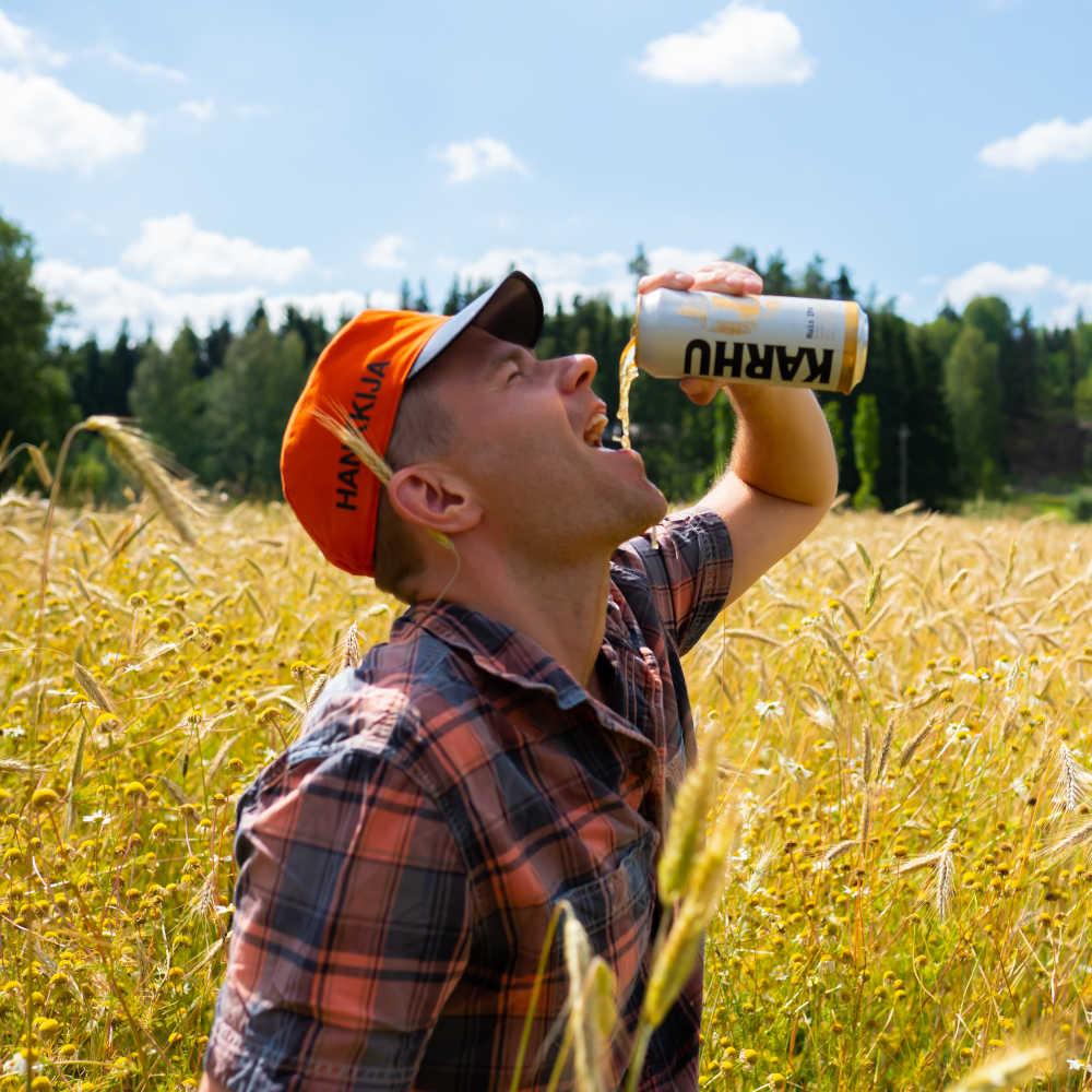 mies juo olutta pellolla